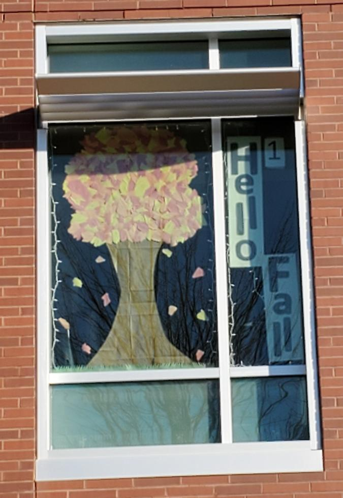 "Window with tree that says ""Hello Fall"""